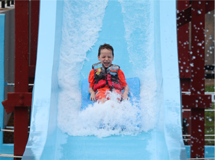 young boy on a mat water slide